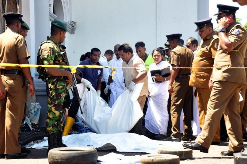 Police officers and rescue workers inspecting the remains of victims after an explosion hit St Anthony's Church in Kochchikade in Colombo, on April 21, 2019.