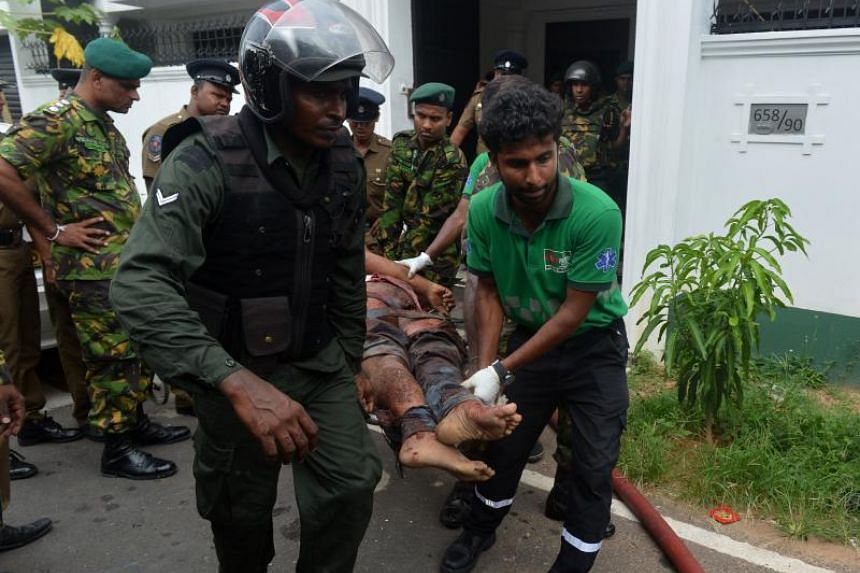 An injured Sri Lankan Special Task Force member is carried by his colleagues after an explosion at a house in Orugodawatta, in Colombo, on April 21, 2019.