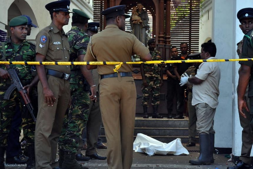 Police and security personnel inspecting casualties at the site of an explosion at St Anthony's Church in Colombo on April 21, 2019.