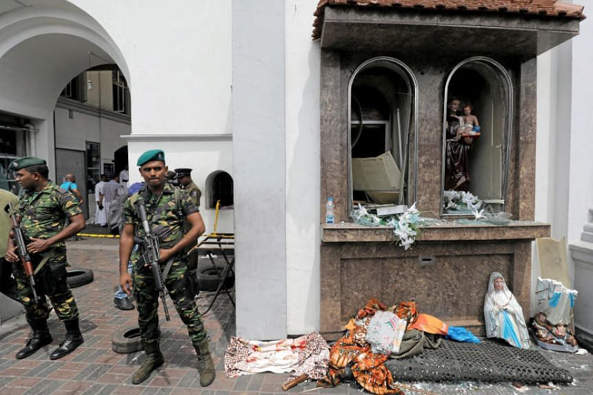 Sri Lankan military officials stand guard in front of St Anthony's Church after an explosion.