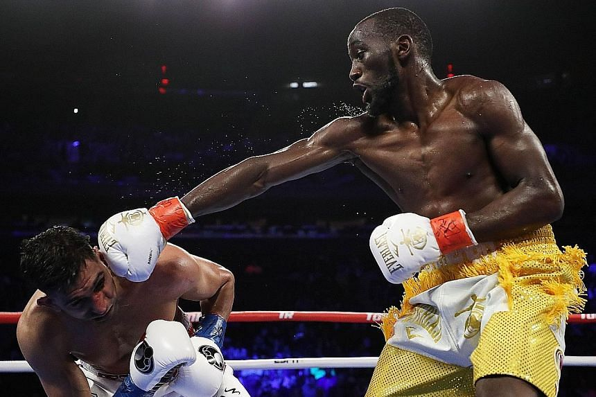 Terence Crawford sends Amir Khan grimacing with a punch at Madison Square Garden on Saturday. The undefeated American retained his WBO welterweight title by a technical knockout.