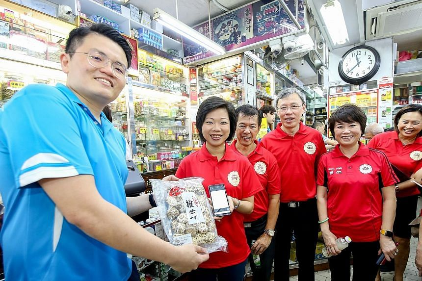 Mr Bobby Ng (far left) with Ms Sim Ann (beside him), Senior Minister of State for Culture, Community and Youth and Communications and Information, and representatives from DBS, Singtel and an industry association, at Thye Hin Hoe Medical Store for the lau