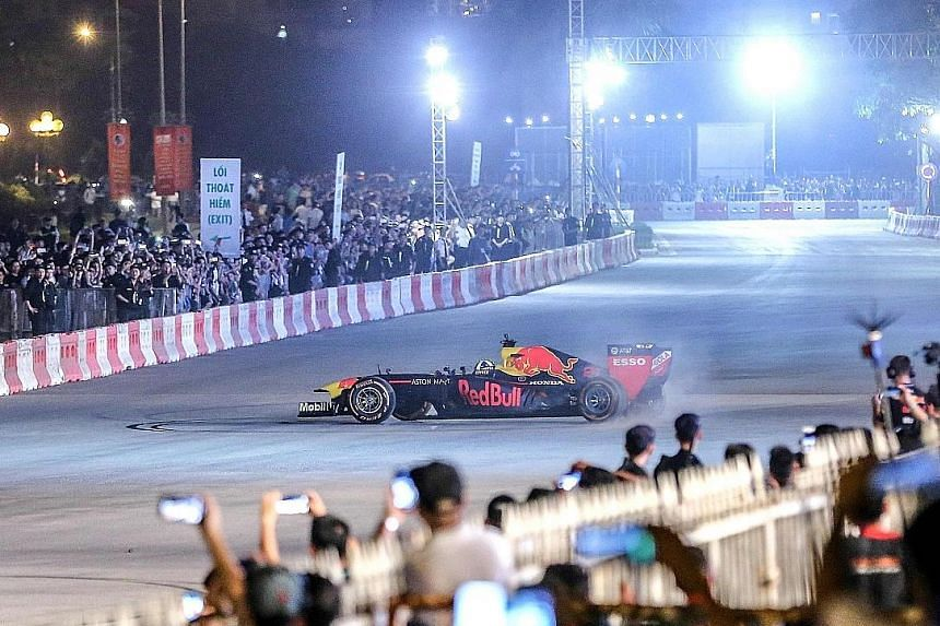 """The crowds in Hanoi getting a taste of Formula One racing on Saturday as David Coulthard performs tricks such as """"doughnuts"""" in his Red Bull car during a preview of next year's Vietnam Grand Prix."""