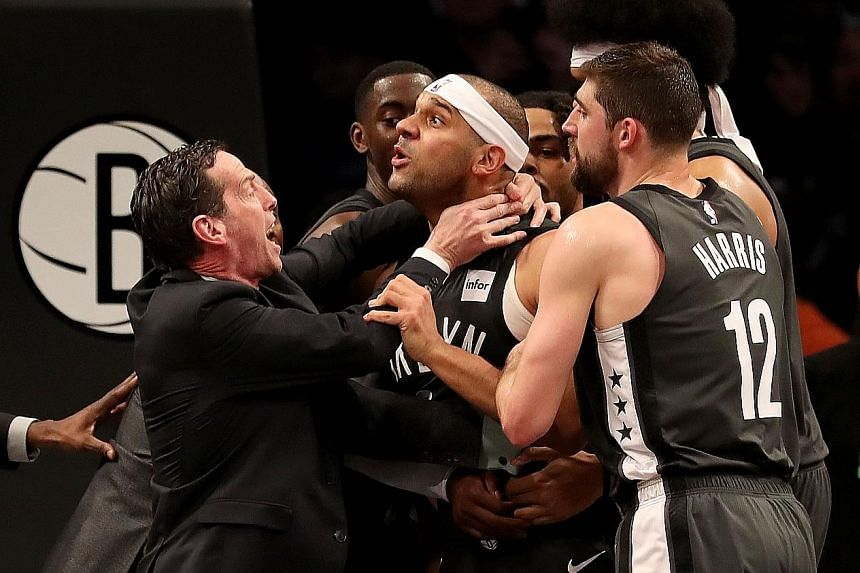 Nets coach Kenny Atkinson and Joe Harris holding back Jared Dudley at Barclays Centre after a foul by Embiid. Dudley and the 76ers' Jimmy Butler were both ejected for escalating the fracas.