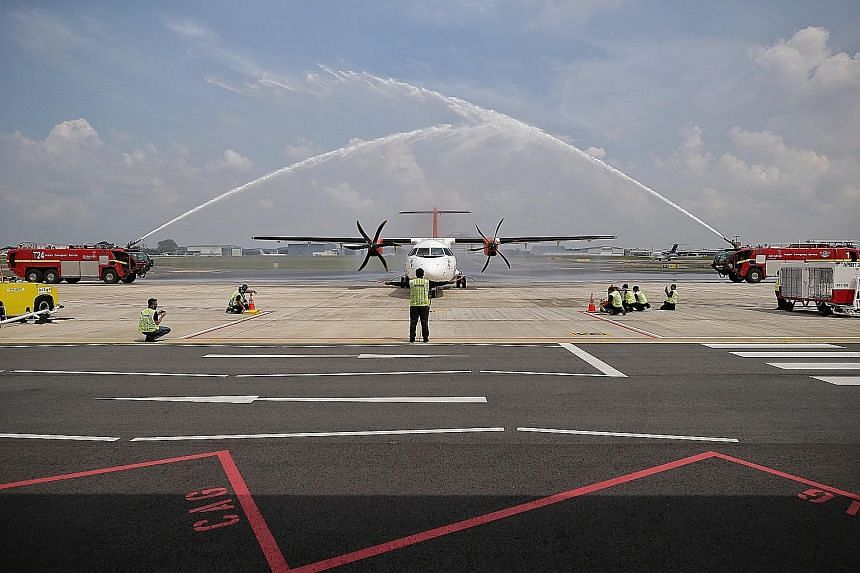 Malaysian carrier Firefly's aircraft receiving a water cannon salute at Seletar Airport after completing its inaugural flight from Subang Airport yesterday. The new GPS-based instrument approach procedures to enhance flight safety at Seletar Airport