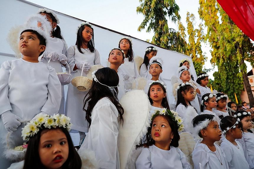 Altar boys preparing to enter the Cathedral of the Good Shepherd in Singapore in a procession at the evening Easter Sunday mass yesterday. ST PHOTO: LIM YAOHUI People at an Easter Sunday mass in tribute to the Notre-Dame cathedral at the Saint-Eustac