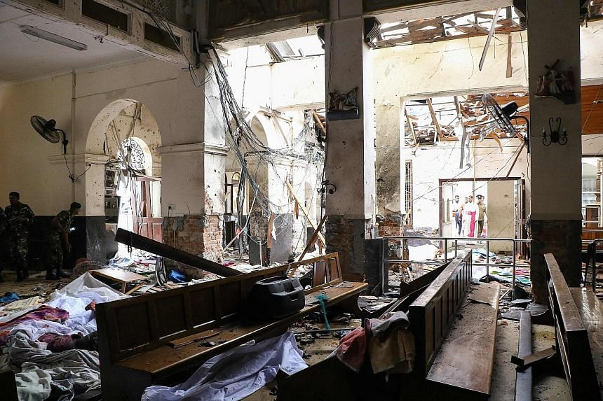 Sri Lankan security personnel at the scene following an explosion at St Anthony's Shrine in Kochchikade in Colombo yesterday, as victims' bodies lay covered with blankets amid the debris.