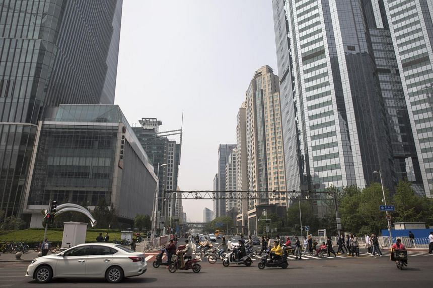 People cross a road in the Central Business District area in Beijing, China, on April 17, 2019.