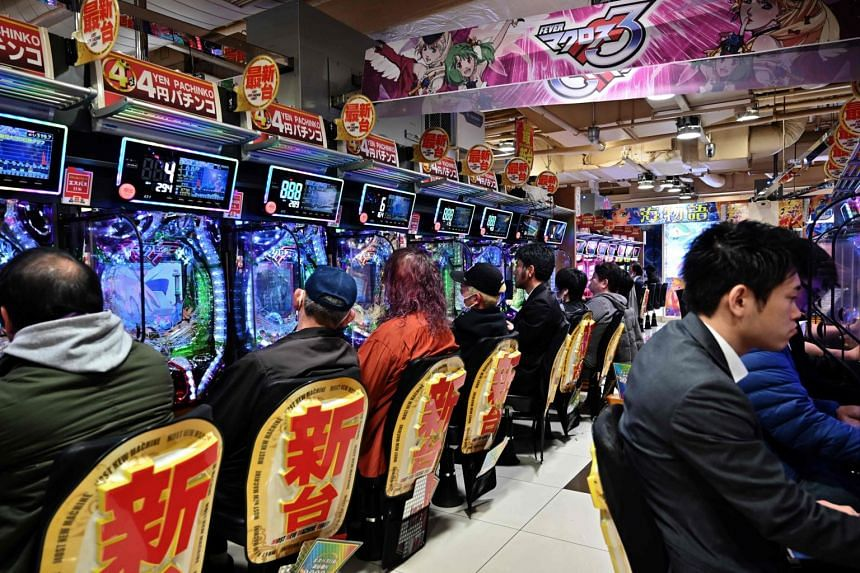 """People sit inside a """"Pachinko"""" parlour in Tokyo's Shinjuku district, on March 22, 2019."""