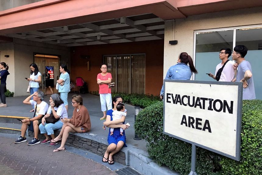 Residents sitting outside their condominium building after being evacuated following an earthquake in Makati City, Philippines, on April 22, 2019.