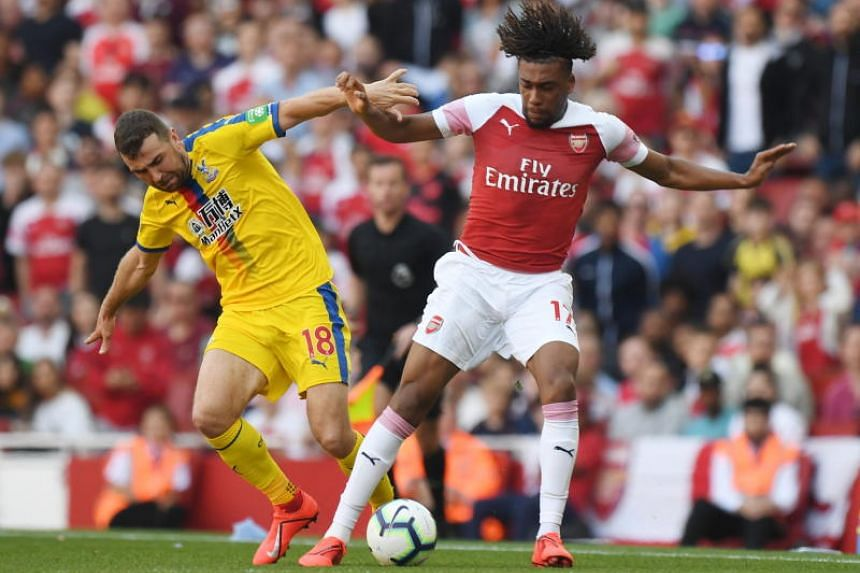 Arsenal's Alex Iwobi (right) vies with Crystal Palace's James McArthur for the ball during the English Premier League soccer match between Arsenal FC and Crystal Palace at the Emirates stadium in London, Britain, on April 21, 2019.