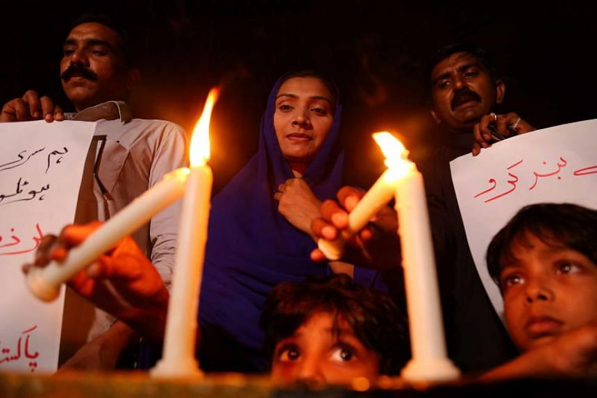 People light candles as they condemn the deadly bomb blasts in Sri Lanka, during a protest in Karachi, Pakistan, on April 21, 2019.