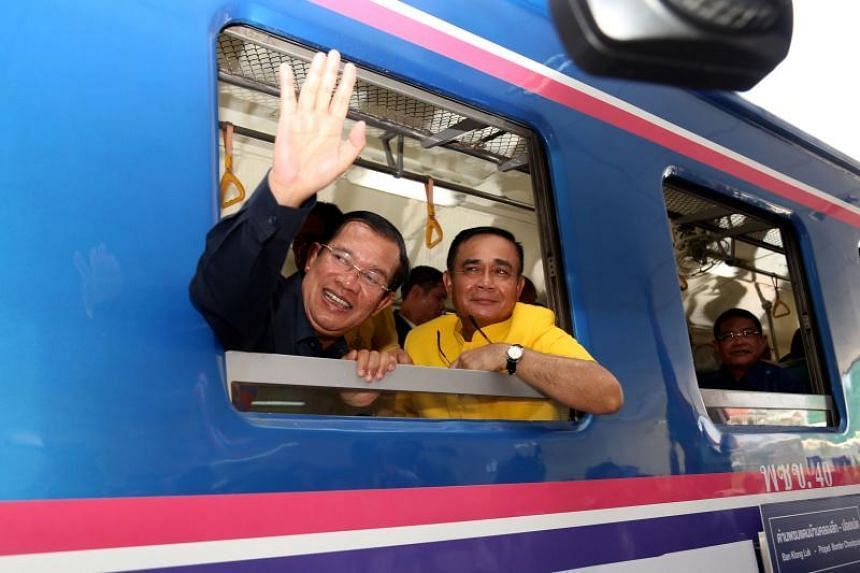 Cambodia's Prime Minister Hun Sen (left) waves beside Thailand's Prime Minister Prayut Chan-O-Cha as they ride a train during a ceremony inaugurating the railway line between Cambodia and Thailand on April 22, 2019.