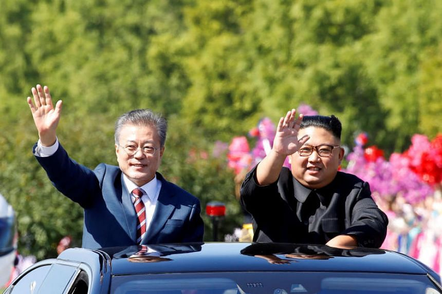 South Korean President Moon Jae-in and North Korean leader Kim Jong Un wave during a car parade in Pyongyang, North Korea, on Sept 18, 2018.
