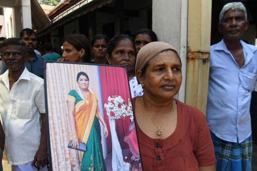 A woman holds a photograph of a bomb blast victim at a morgue in Colombo on April 22, 2019, as people gather hoping to identify loved ones missing or killed in the Easter Sunday bomb attacks on churches and hotels.