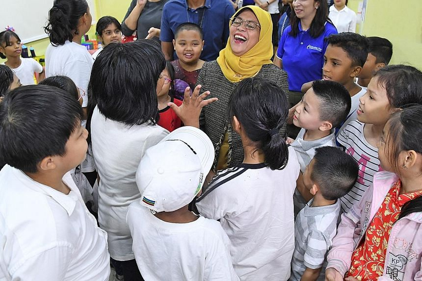 President Halimah Yacob interacting with children enrolled in the CareNights@Morning Star programme at Morning Star Community Services' Bedok North Centre yesterday. Under the programme, children get homework supervision and take part in various acti