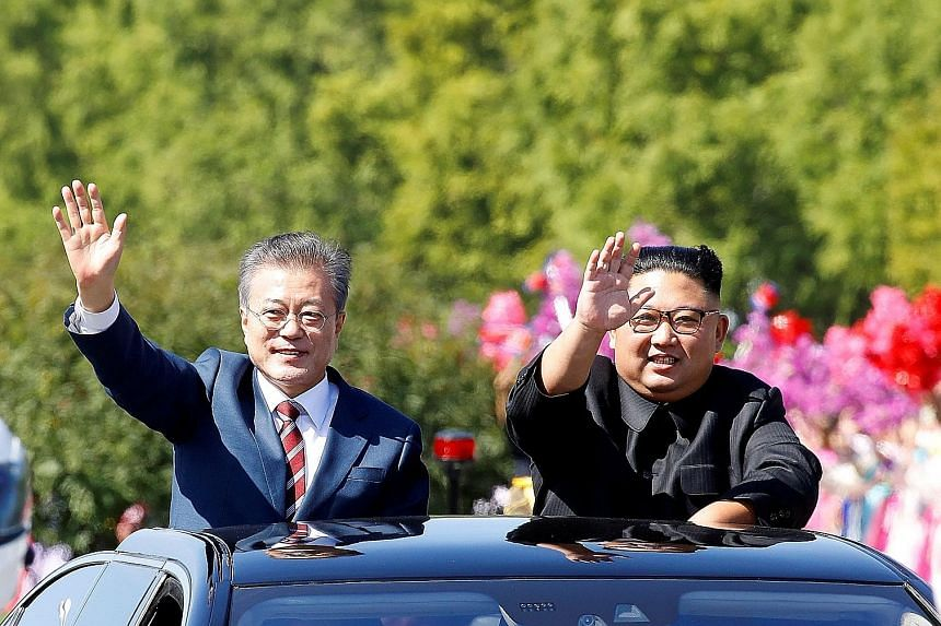 South Korean President Moon Jae-in (left) and North Korean leader Kim Jong Un at a parade in Pyongyang last September. Seoul will celebrate the anniversary of last year's inter-Korean summit on Saturday at Panmunjom, where the summit was held, but wh