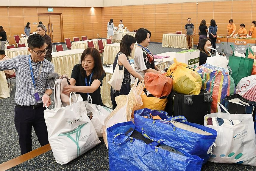 The Straits Times travel writer Lee Siew Hua (second from left) donating a large bag of clothes during the textile donation drive at SPH's Earth Day 2019 yesterday - an annual environmental awareness event organised by Singapore Press Holdings. About
