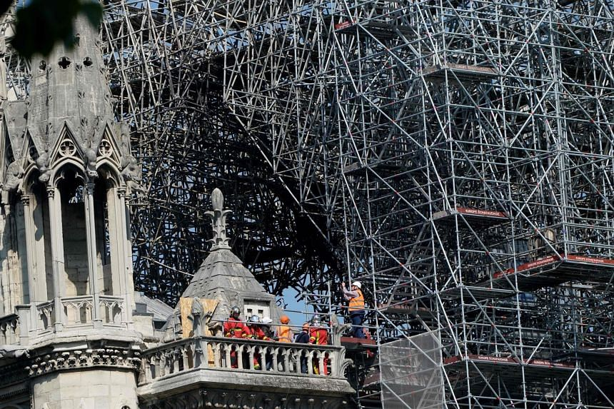 Firefighters working on a balcony of Paris' Notre-Dame cathedral last Friday, four days after a fire destroyed its spire and roof. France plans to rebuild the iconic cathedral in just five years, for it embodies not only the religious spirit of those