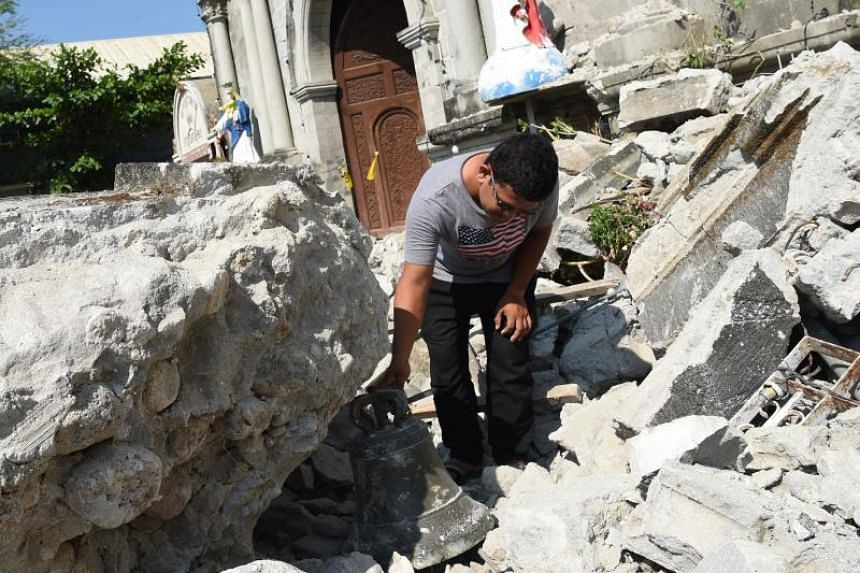 A church worker inspects a bell from the 18th century St Catherine of Alexandria after its bell tower was destroyed following an earthquake in the town of Porac in the Philippines' Pampanga province on April 23, 2019.