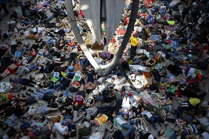 "Extinction Rebellion climate change activists perform a mass ""die-in"" under the blue whale in the foyer of the Natural History Museum in London, on April 22, 2019."