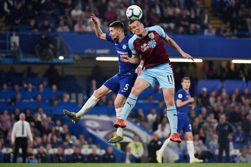 Chelsea's Jorginho (left) vies for the ball with Burnley's Chris Wood during a Premier League soccer match at Stamford Bridge in London, Britain, on April 22, 2019.