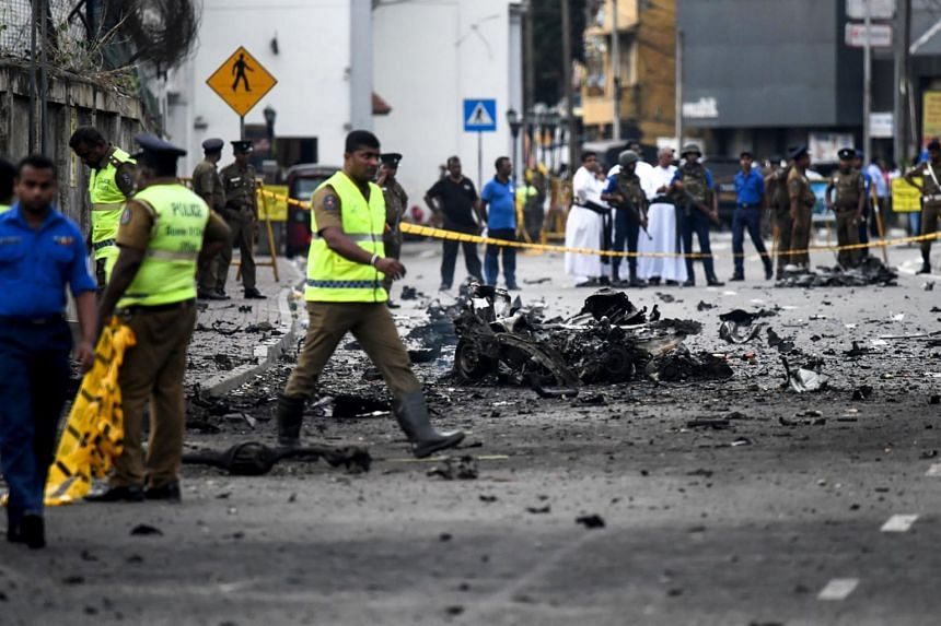 Sri Lankan security personnel inspecting the debris of a car after it exploded near St Anthony's Shrine in Colombo, on April 22, 2019.