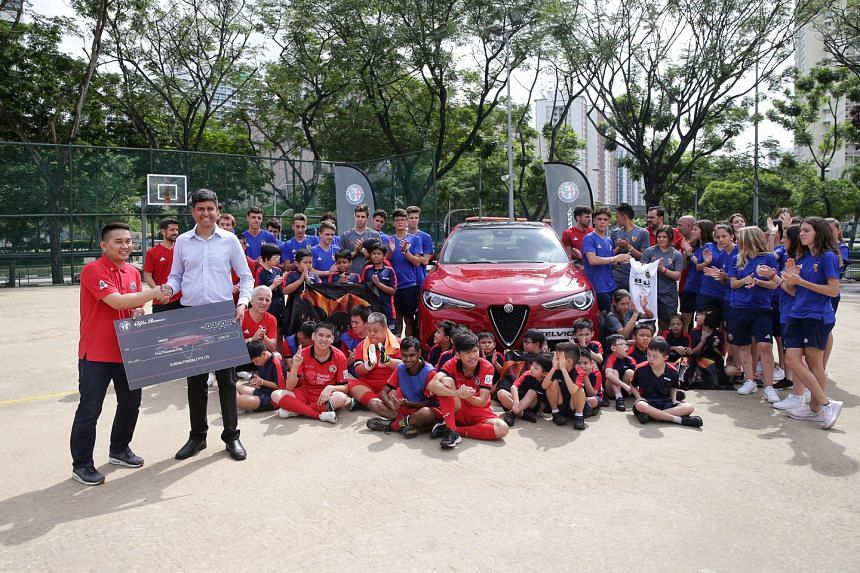 Jay Ravi (left), sales manager of Alfa Romeo, presenting a cheque to Fernvale Gardens School principal Gerard Vaz after a clinic conducted by Valencia youth footballers and coaches for Minds children yesterday.
