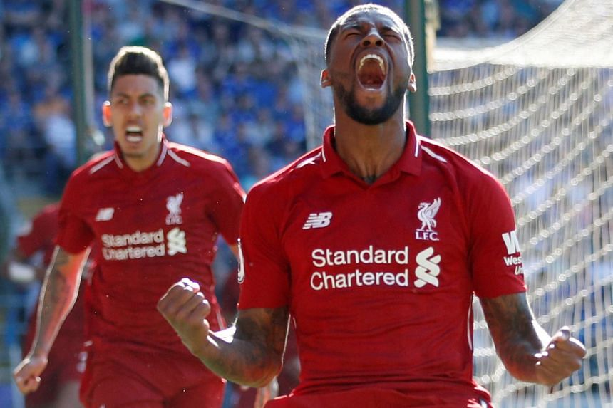 Georginio Wijnaldum celebrates scoring Liverpool's first goal against Cardiff in their Premier League match, as Roberto Firmino rushes to join in. The Reds won 2-0 to put the pressure back on champions Manchester City.