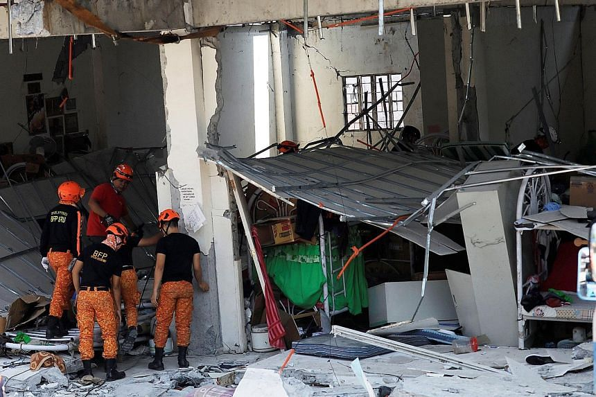 Rescuers at a collapsed four-storey building following the earthquake in Porac town, Pampanga province. PHOTO: REUTERS