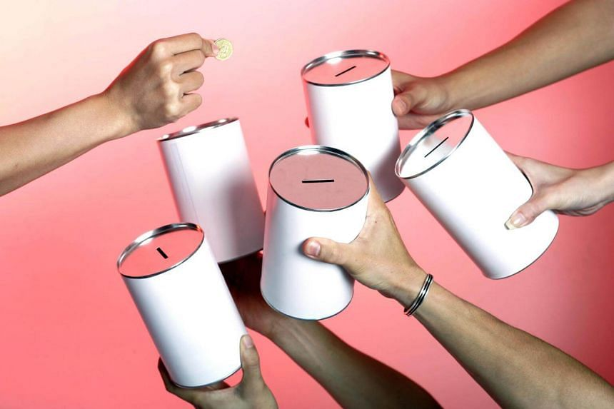 Posed photo showing donation tins and the hand of a donor.