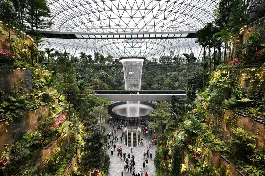 Members of the public viewing the Rain Vortex at Jewel Changi Airport.