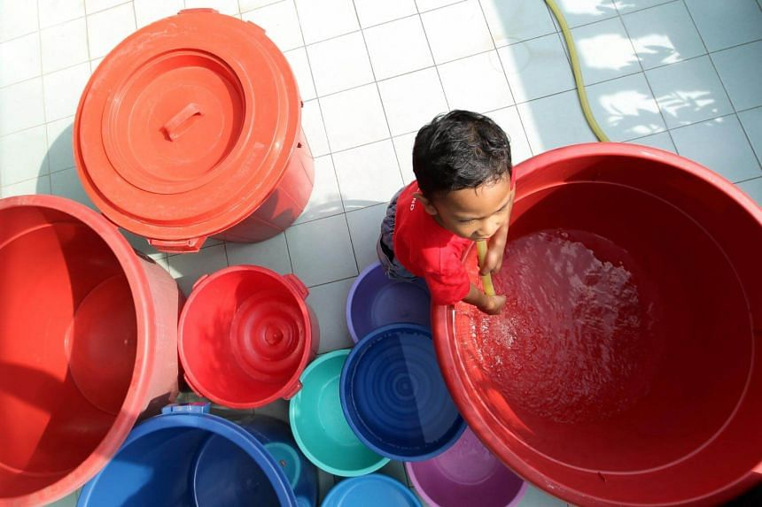 A boy filling pails with water in the Klang Valley in 2016.