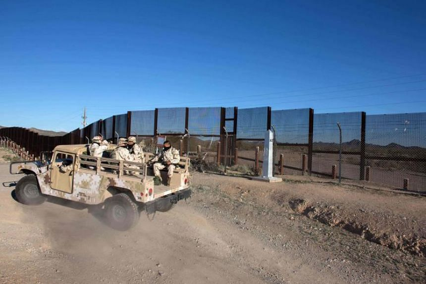 Mexican soldiers drive along a section of the US/Mexico border fence in Sonoyta, Mexico on Feb 16, 2017.