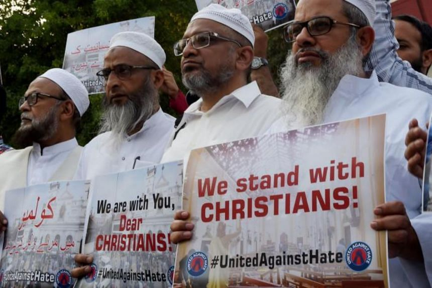 Indian Muslims hold placards outside the Sacred Heart Cathedral as they pay tribute to the victims of the Sri Lankan terror attacks, in New Delhi on April 23, 2019.
