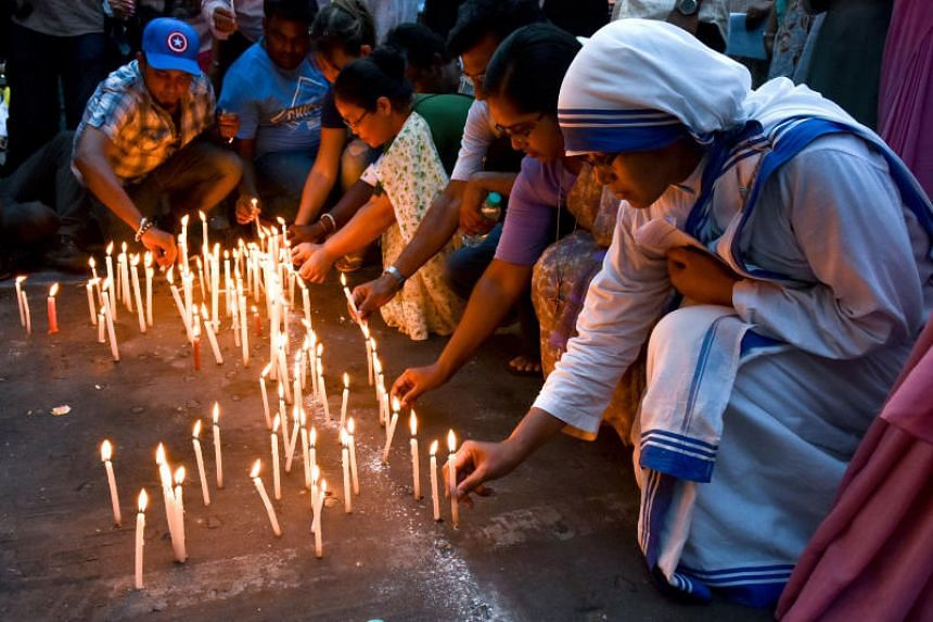 People light candles during a remembrance ceremony held for the victims of the suicide bombings in Sri Lanka.