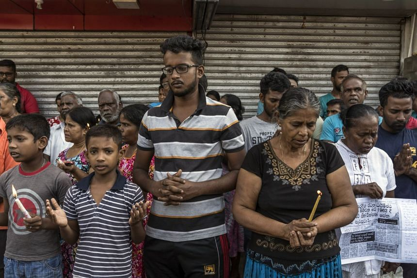 People gather outside St Anthony's Church in Colombo to observe a nationwide three minutes of silence.