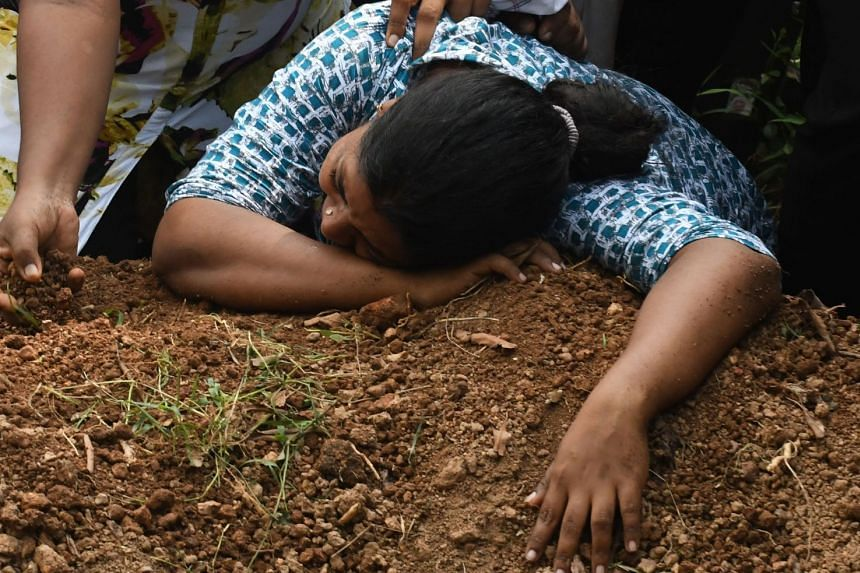 A Sri Lankan woman cries during a burial service for a bomb blast victim at a cemetery in Colombo.