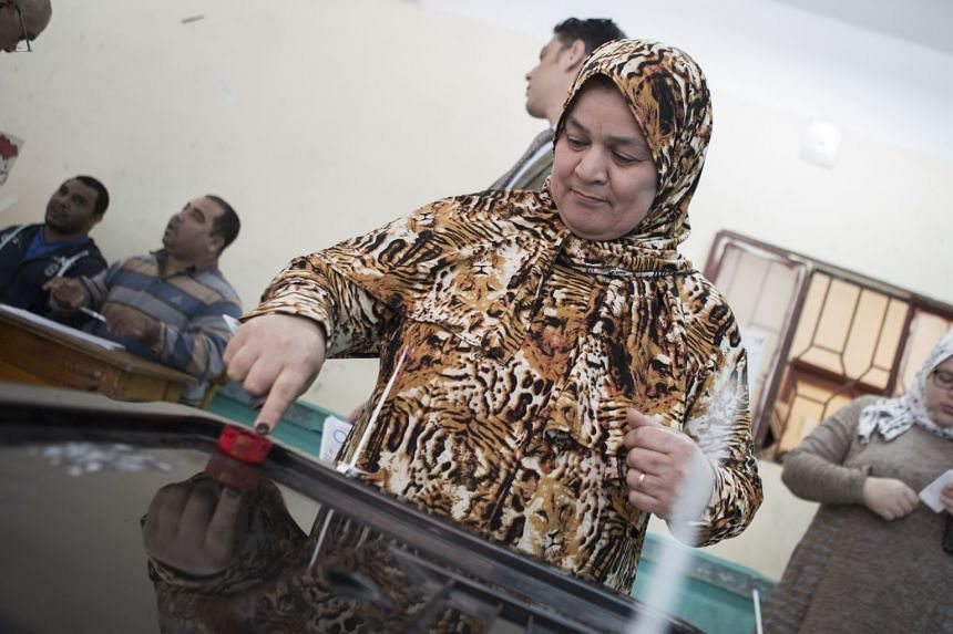 A woman puts her finger in ink during the first day of voting in the national referendum on Sisi's term.