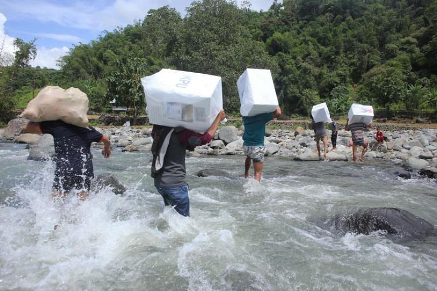 Indonesian workers transport ballot boxes for the general elections at the Bonto Matinggi village, Maros, South Sulawesi on April 16, 2019.