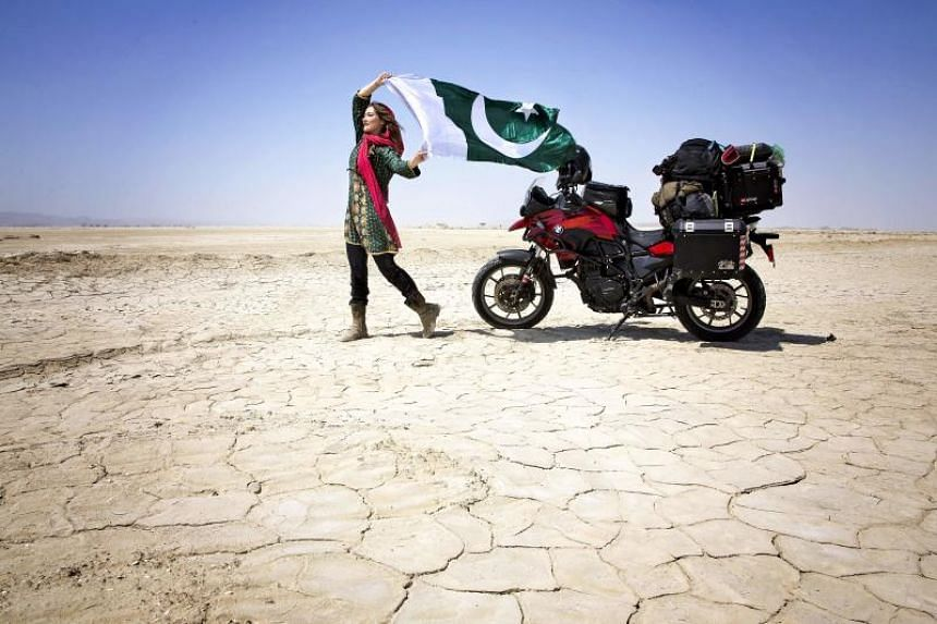 Canadian tourist Rosie Gabrielle poses for photographs as she holds a Pakistani flag during her motorcycle trip in southwestern Balochistan province in Pakistan.