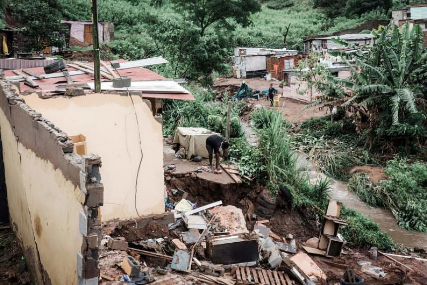 People begin to remove debris after their homes were destroyed by torrential rains and flash floods at an informal settlement of Bottlebrush, south of Durban, on April 23, 2019.