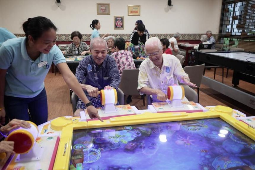 Healthcare assistant Ms Moh Moh guiding (from left) Mr Robin Liow, 72, and Mr Teo Cheng Lok, 85, who are playing an arcade game at the games room in the senior care centre at Ghim Moh on April 24, 2019.