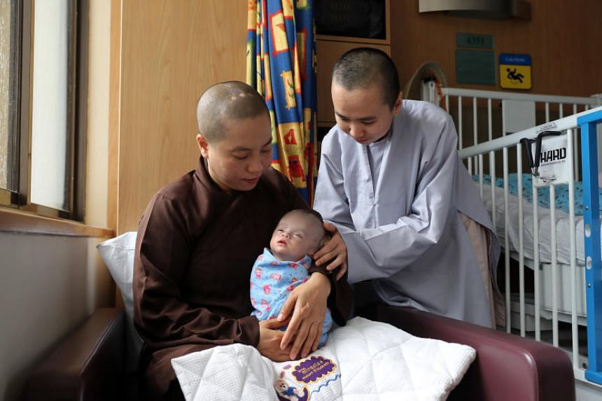 (From left) Venerable Minh Tai 41, abbot of Hue Quang Monastery in Da Lat City with baby Trieu Hoai An and assistant nun Thien Ngo, 24.