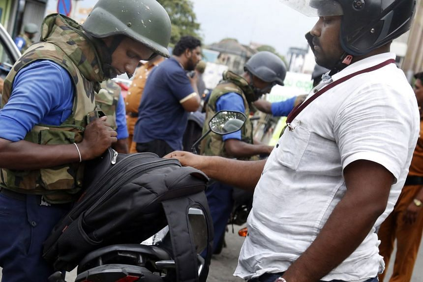 Sri Lankan security personnel check bags in Colombo, April 25, 2019.