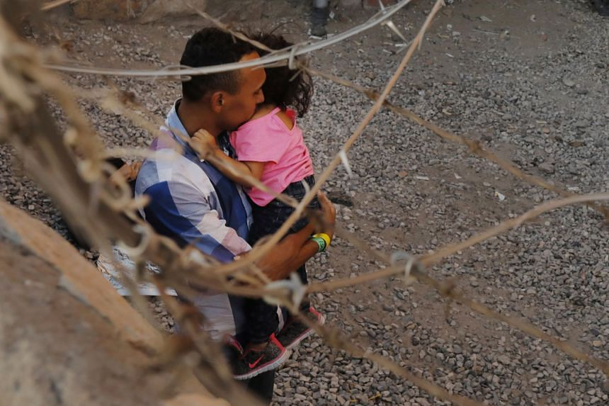 A man holds a child inside an enclosure in El Paso, Texas, where they are being held by US Customs and Border Protection, after crossing the border between Mexico and the US illegally and turning themselves in to request asylum.