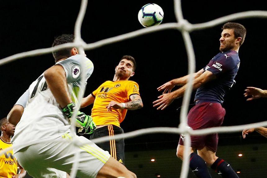 Arsenal's Sokratis Papastathopoulos scores their first goal.