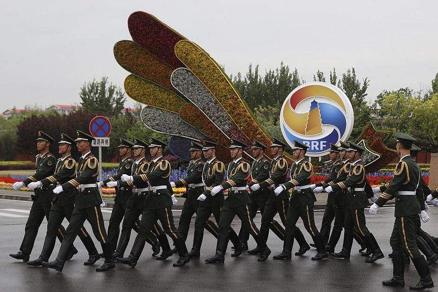 Chinese paramilitary personnel marching past a decor for the Belt and Road Forum outside the special plane terminal of the Beijing International airport. The summit, which starts today, boasts a hefty guest list of world leaders, including from all 1