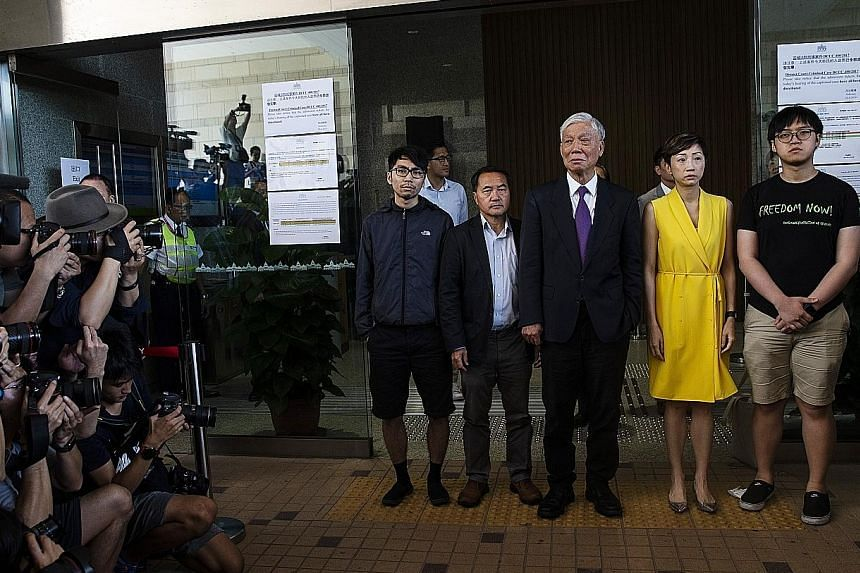 """From left: Democracy activists Tommy Cheung, Lee Wing Tat, Chu Yiu Ming, Tanya Chan and Eason Chung outside the West Kowloon Law Courts in Hong Kong yesterday. The judge said their """"martyrdom ... was a concocted one"""", noting that the price the defend"""