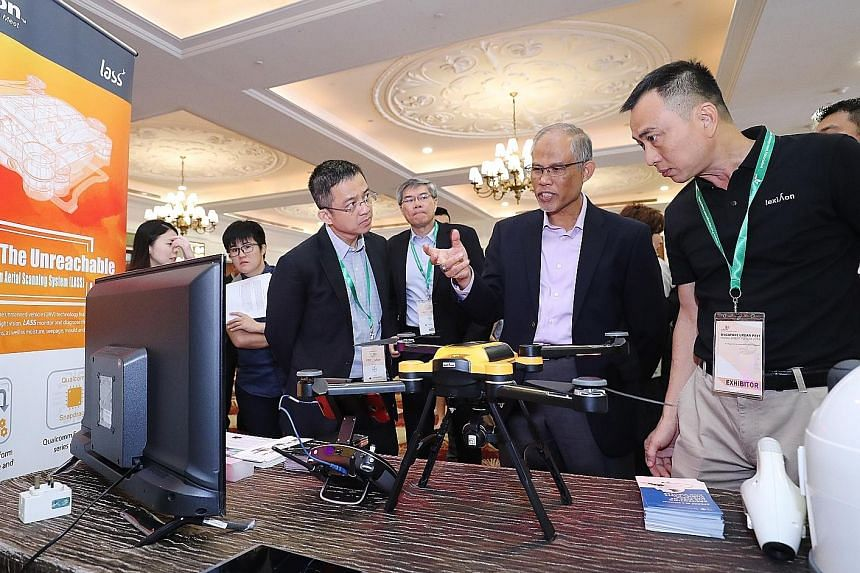 Minister for the Environment and Water Resources Masagos Zulkifli checking out a drone that helps to detect mosquito breeding grounds, at the event yesterday. With him are (from left) Mr Tan Meng Dui, chief executive of the National Environment Agenc